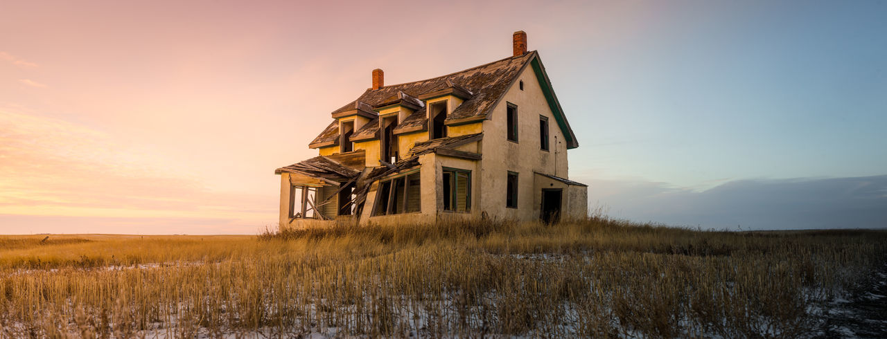 Abandoned house on field against sky during sunset
