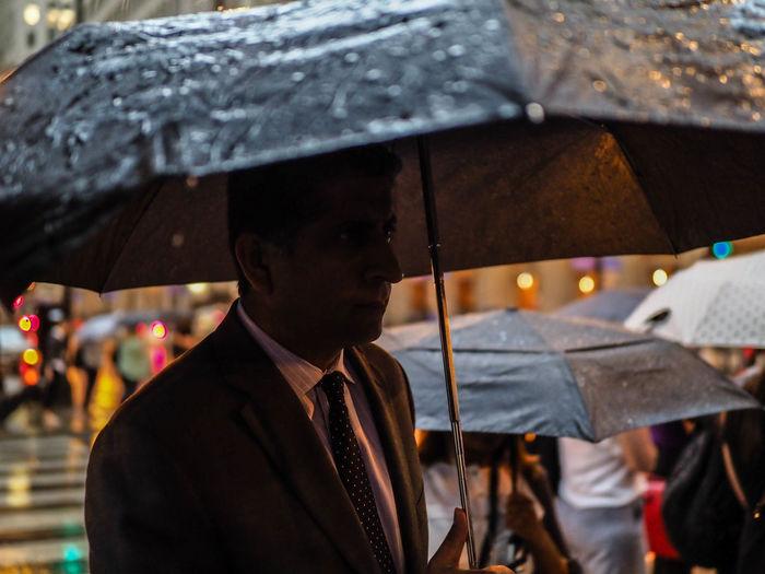 Portrait of man holding umbrella during rainy season