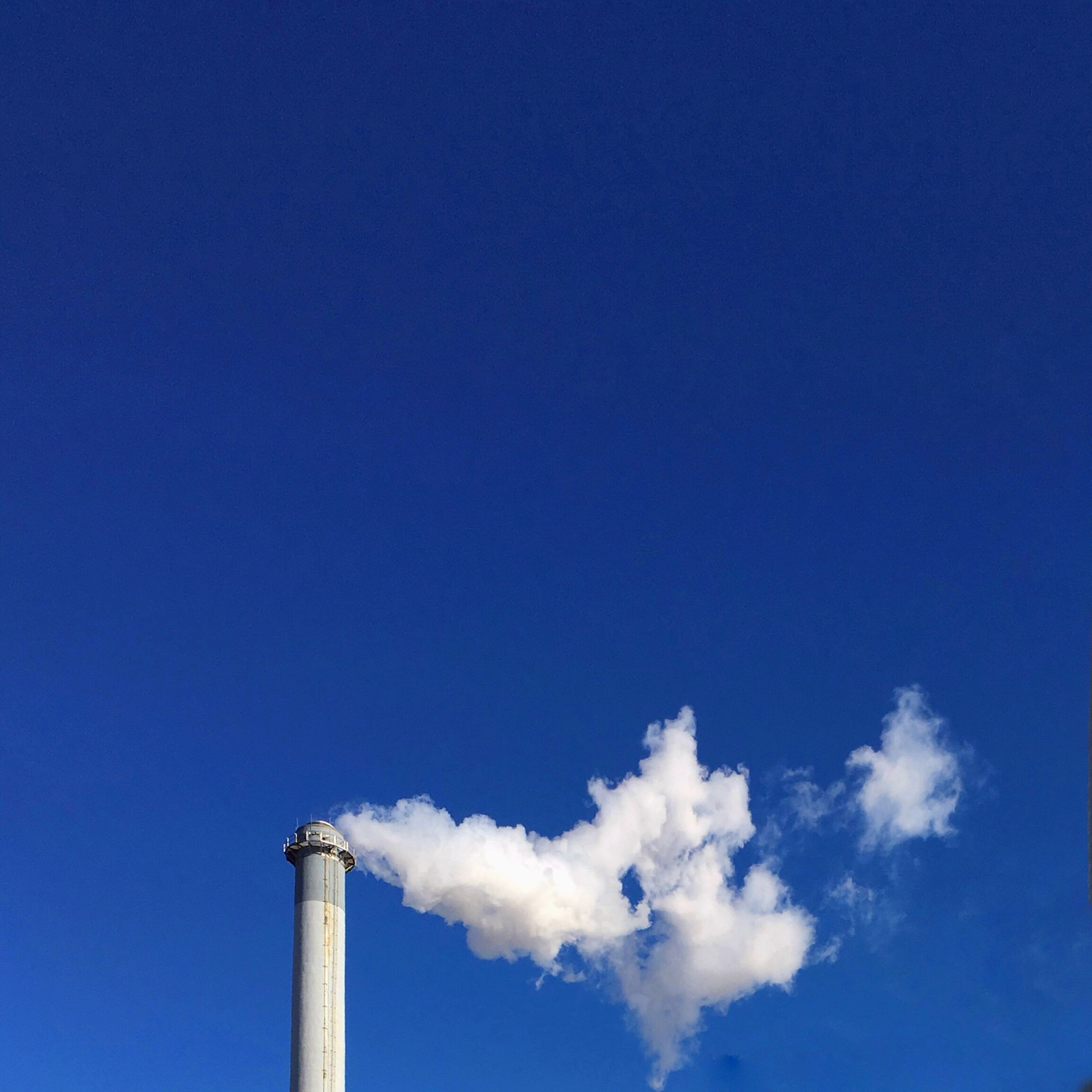 low angle view, blue, copy space, clear sky, sky, built structure, day, no people, pole, high section, outdoors, architecture, smoke stack, cloud, nature, sunlight, chimney, cloud - sky, tranquility, vapor trail