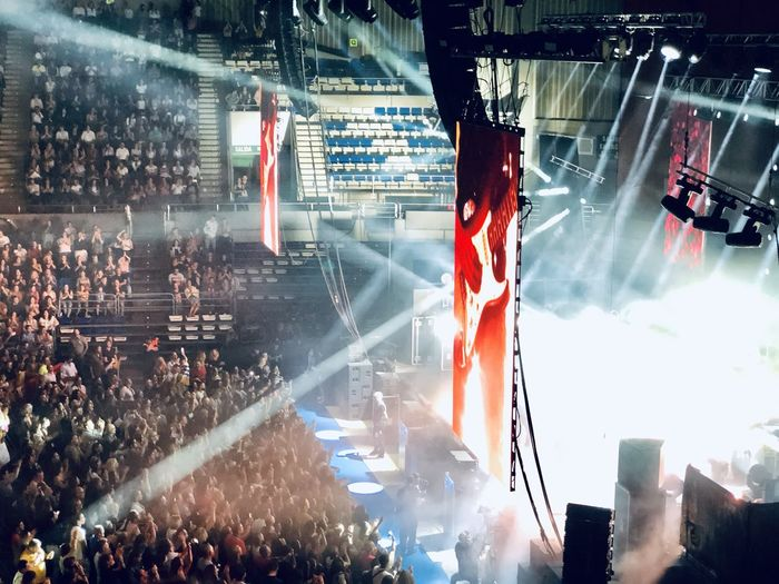 Panoramic view of crowd at music concert at night