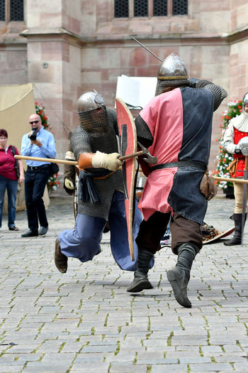 People looking at men in period costume fighting during knight tournament