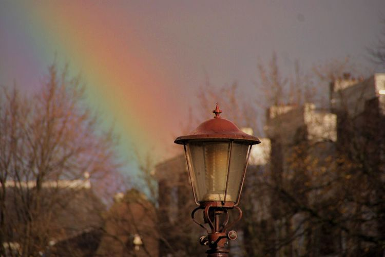 Close-Up Of Street Light Against Rainbow At Dusk