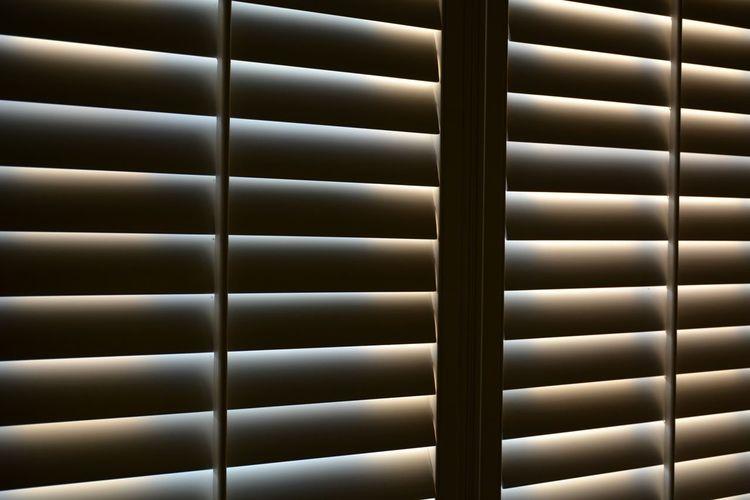 Full frame shot of sunlight through closed plantation shutters