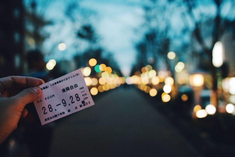 Close-up of hand holding illuminated ticket