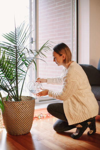 Side view of woman watering plant at home