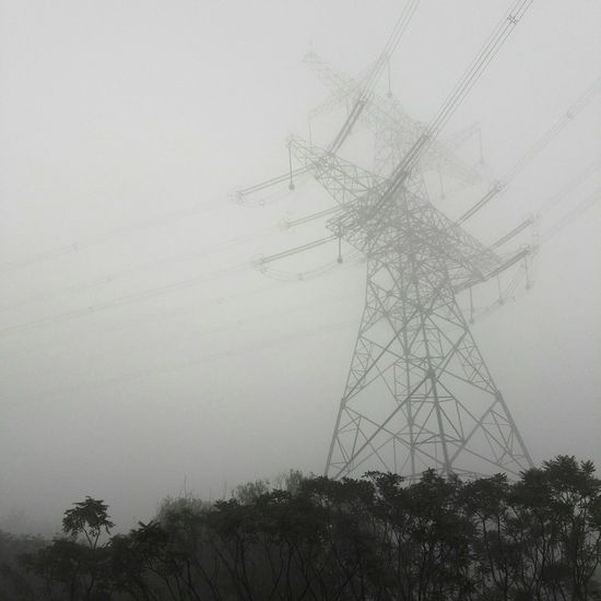 Low angle view of electricity pylon against sky during foggy weather