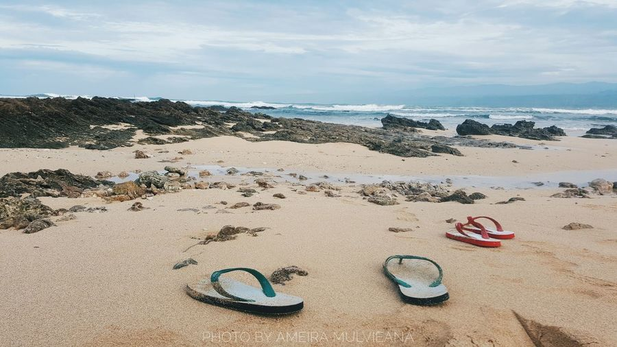 High angle view of shoes on beach against sky