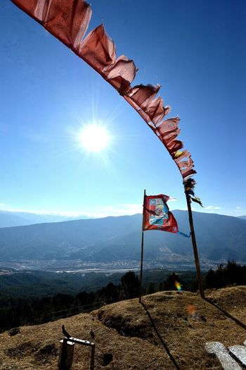 Low angle view of flag on mountain against blue sky