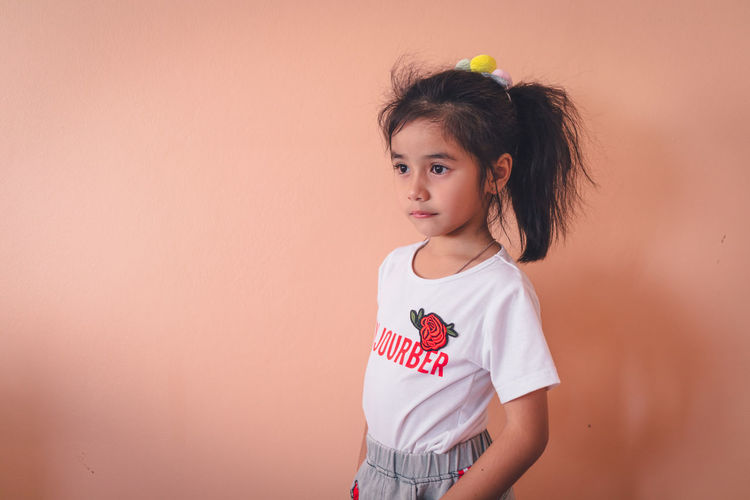 Portrait of cute girl standing against wall