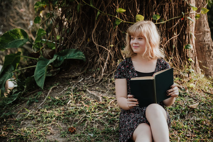 Smiling young woman looking away while holding book in forest