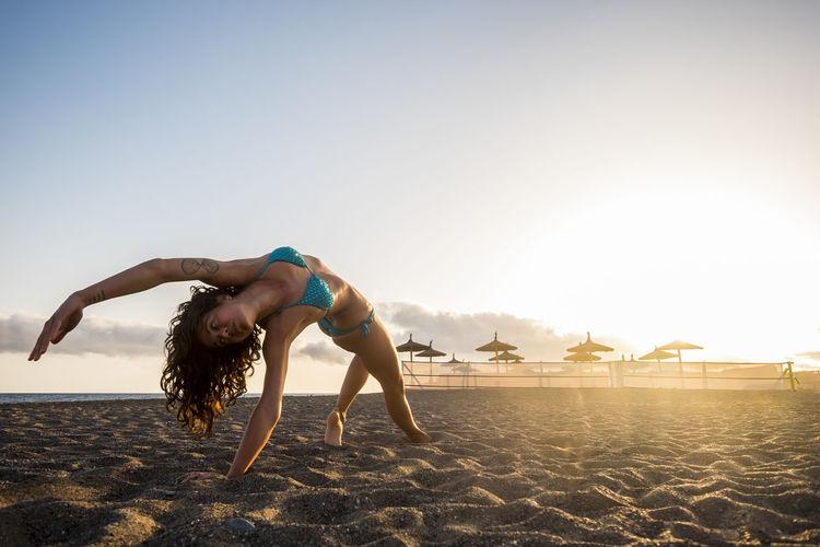 Full length of woman exercising at beach against sky