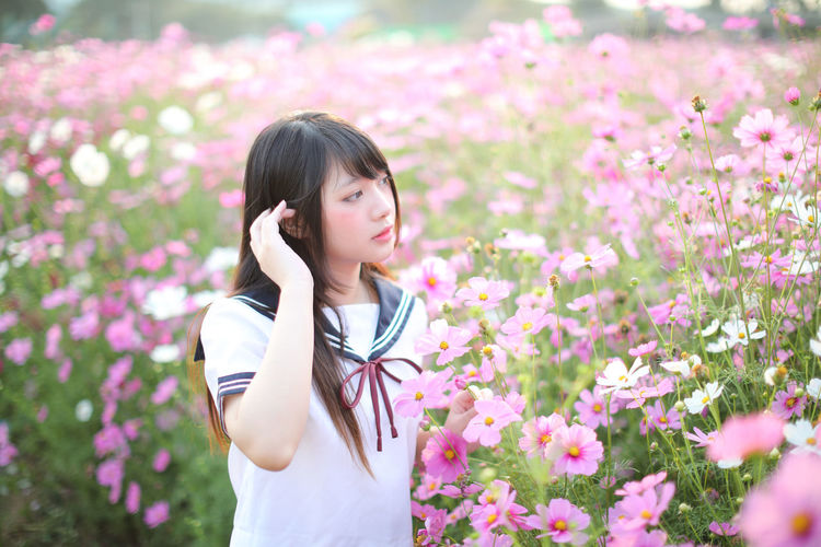 Beautiful woman standing by pink flowering plants