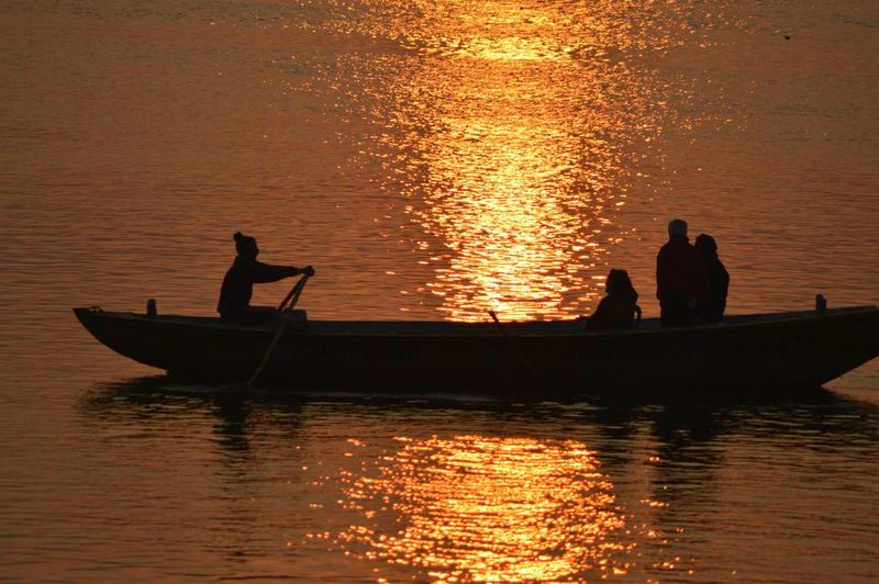 Silhouette people sailing on boat in lake during sunset