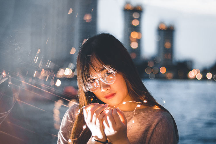 Portrait of woman holding illuminated string lights in city