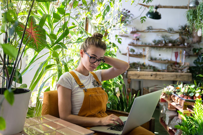 Woman using laptop while sitting amidst plants in workshop