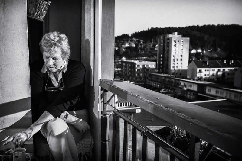 Senior Woman Sitting By Railing On Balcony