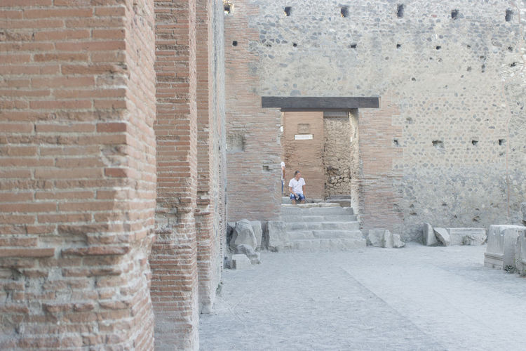 Man walking by historic building