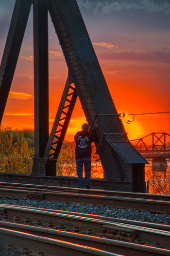 Man standing on railroad track against sky during sunset