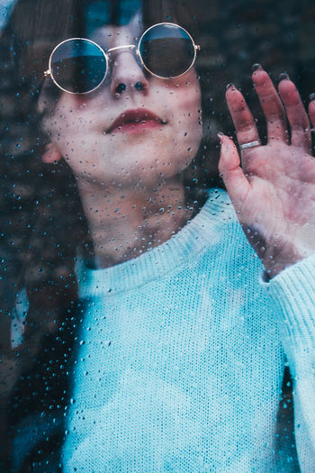 Woman wearing sunglasses seen though wet window