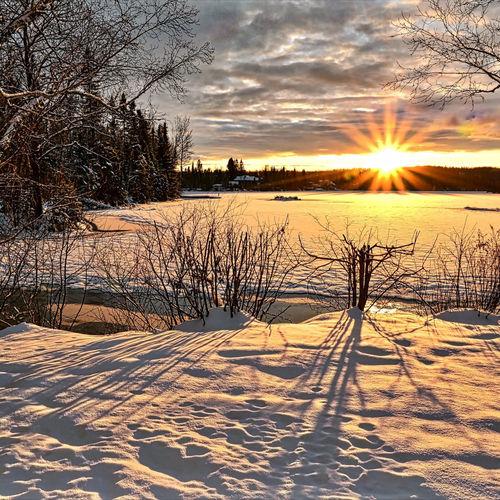 Frozen lake against sky during sunset