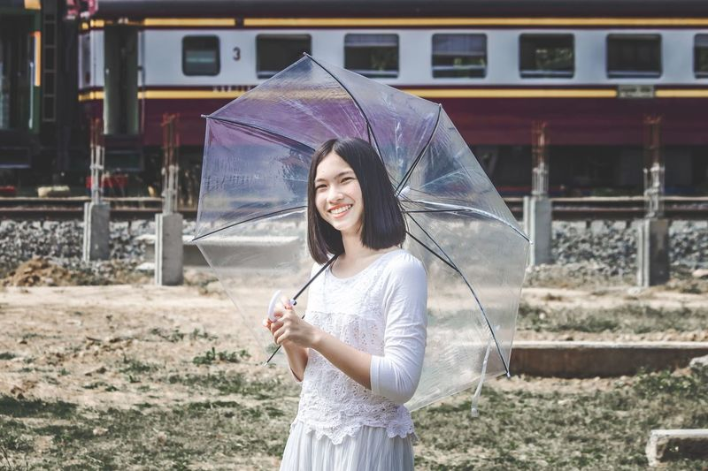Portrait of smiling young beautiful women holding umbrella standing in front of train.