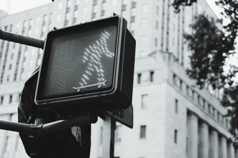 Low angle view of road signal against building in city