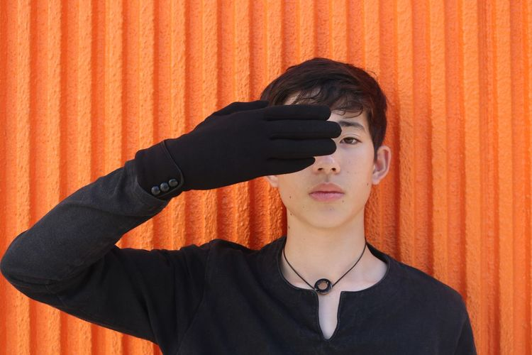 Portrait of young man wearing sunglasses standing against orange wall