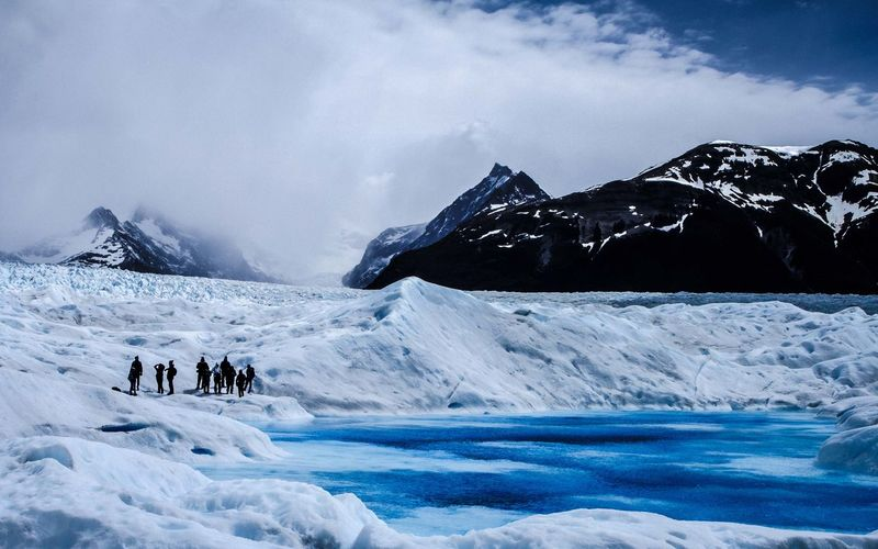 Hikers at perito moreno glacier against sky