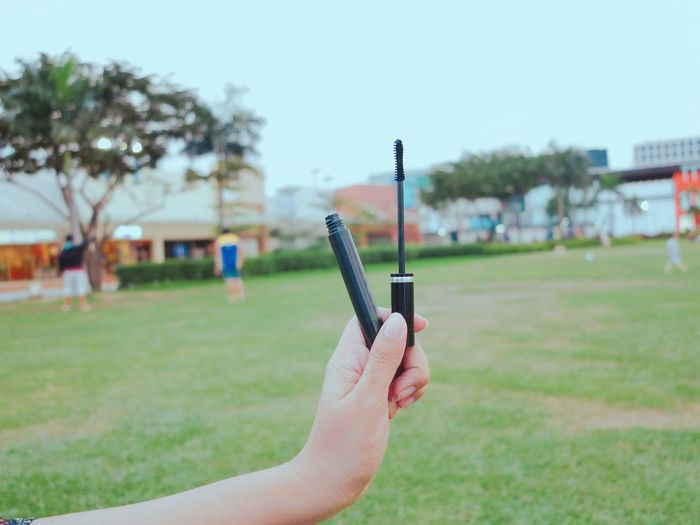 Mascara ❤️ Communication Wireless Technology Mobile Phone Human Hand Smart Phone Portable Information Device Focus On Foreground Real People One Person Holding Using Phone Cellphone Human Body Part Day Outdoors Close-up Grass Sky People Adult Mascara Makeup