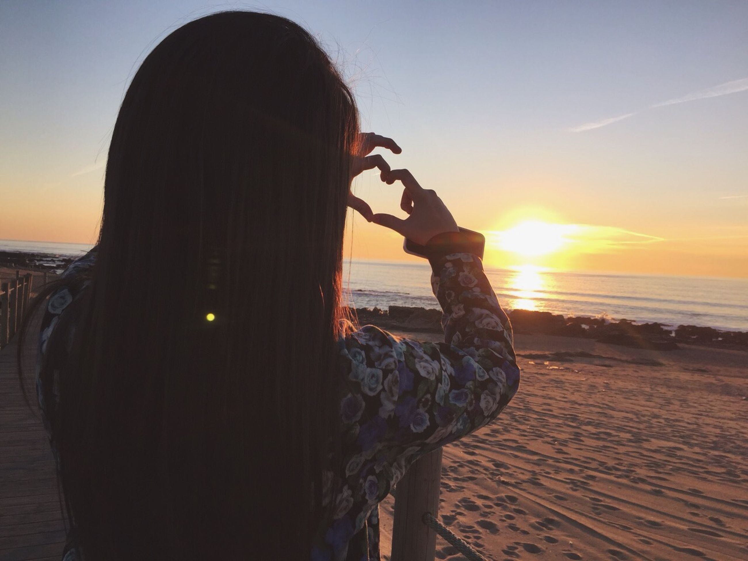sunset, sea, beach, lifestyles, leisure activity, water, sun, horizon over water, sky, shore, silhouette, sunlight, vacations, orange color, person, scenics, beauty in nature, standing