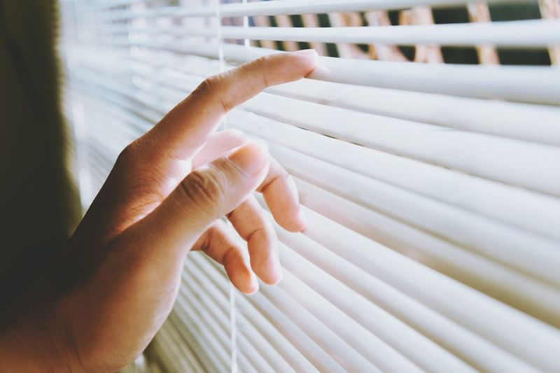 Cropped Hand Touching Window Blinds