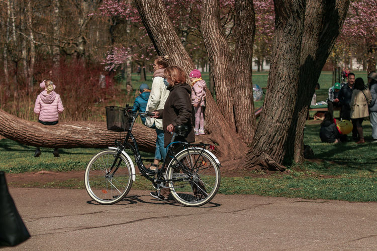 People sitting on bicycle by tree trunk
