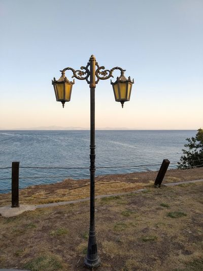 View of street light on beach against clear sky