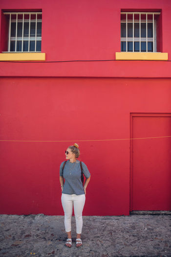 Full length of woman standing against red wall