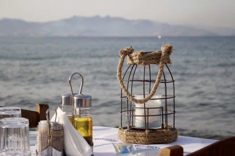 Lantern by olive oil in container on table against sea