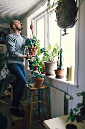 Man and potted plants on table at home