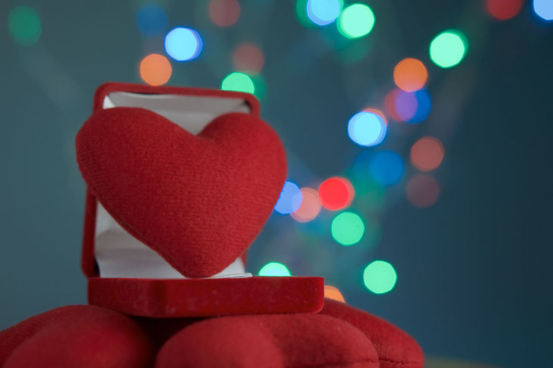 Close-up of heart shape in box against defocused multi colored lights