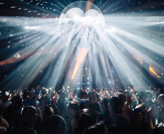 Illuminated Disco Ball Over Crowd At Nightclub