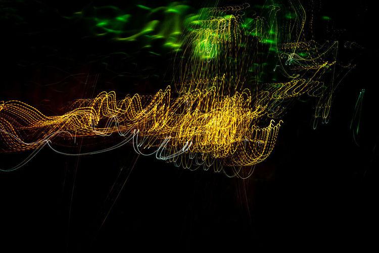 Close-up of illuminated light trails against black background