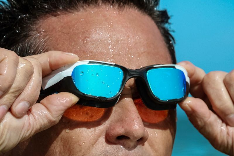 Close-up of man removing swimming goggles