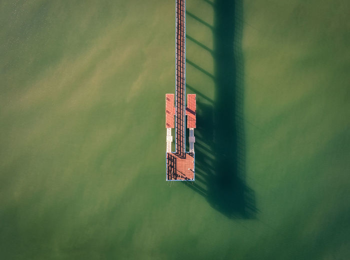 Fishermen on a pier in the middle of green sea water at sunrise with long shadows