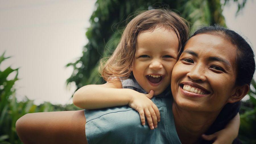 Portrait of happy mother piggybacking daughter