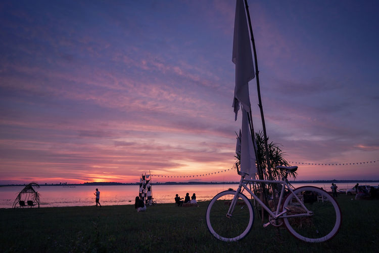 Silhouette bicycle on beach against sky during sunset