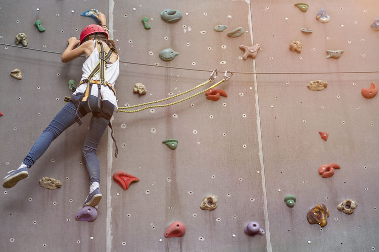 Activity Balance Bouldering Climbing Climbing Wall Danger Extreme Sports Female Fitness Girl Helmet Hobby Indoors  Leisure Leisure Activity Lifestyles One Person Outdoors Risky Saftey Sport Teenager Training Water Woman