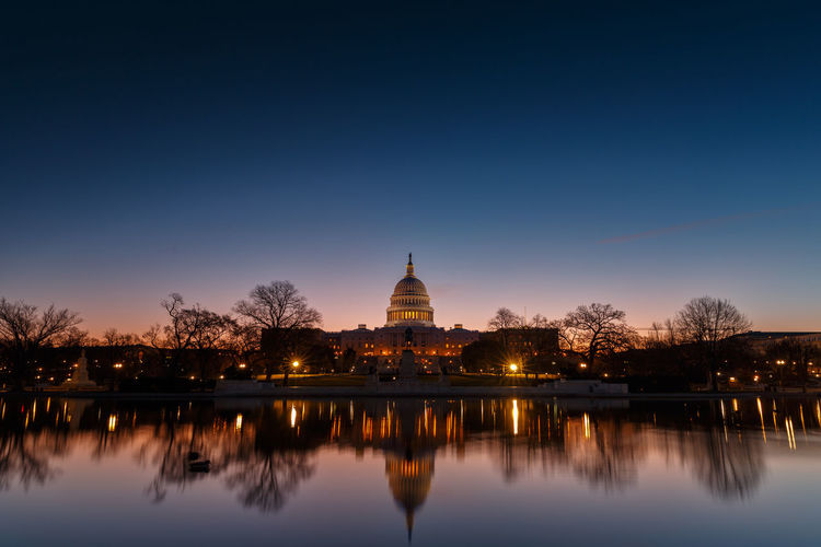 Illuminated United States Capital Dome With Reflection On River At Dusk
