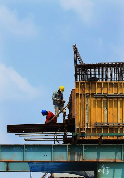 Low angle view of workers working at construction site against sky