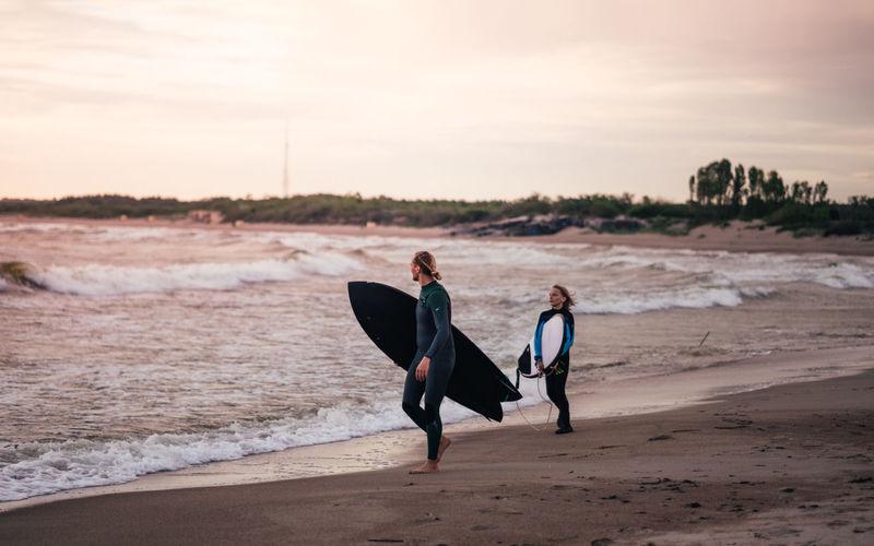 Men walking on beach against sky during sunset