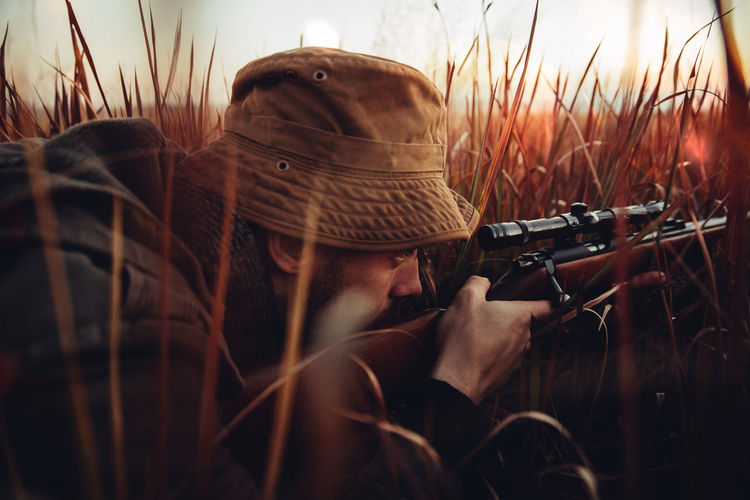Agriculture Field Focus On Foreground Gun Hunter Hunting Laying Leisure Activity Lifestyle Man Mature Meat Nature Outdoors People Pointing Prey Rural Scene Selective Focus Skill  Sniper Sunflare Sunrise Weapon