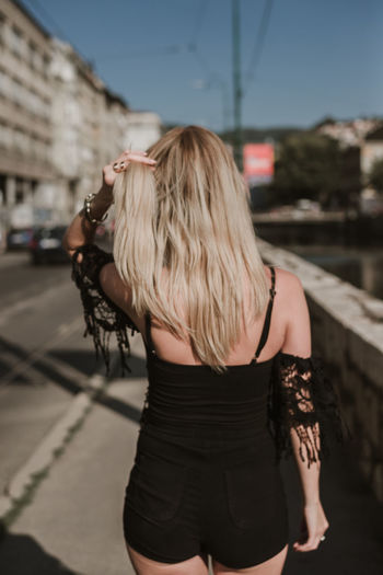 Rear View Of Woman With Blond Hair Standing In City