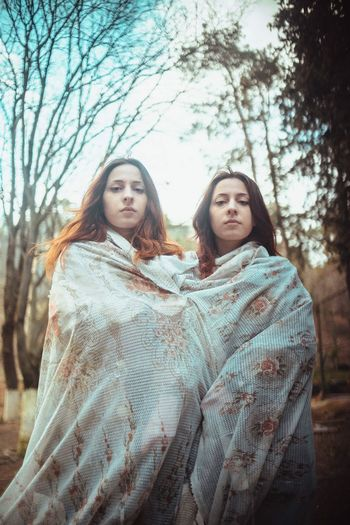 Portrait of sisters wrapped in blanket standing against trees